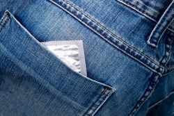 Close-up of a condom peeking out of the back pocket of blue jeans Soft focus