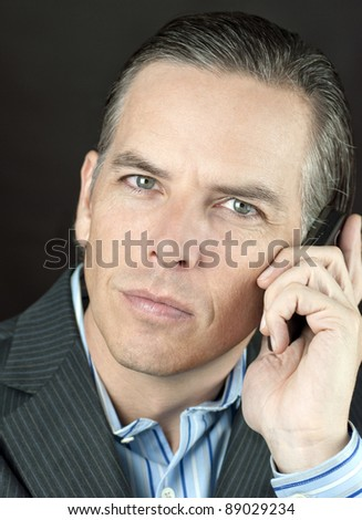 Close-up of a confident businessman taking a call looking at camera.