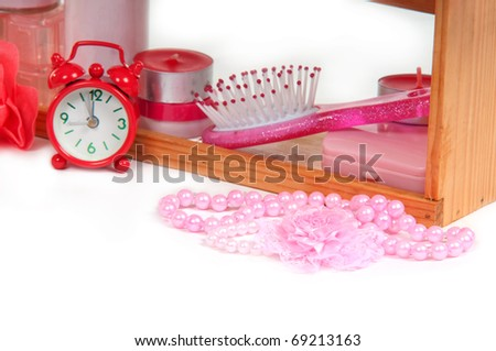 Close-up of a cosmetic shelf with pink bath accessories and alarm clock standing on wooden shelf isolated on white background