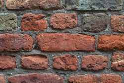 Close-up of a cottage wall featuring handmade clay reddish brown bricks