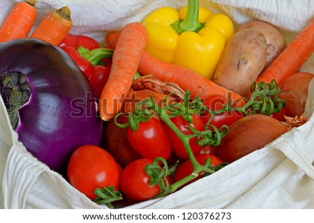 Close up of a cotton shopping bag full of fresh vegetarian food of different color for healthy lifestyle.
