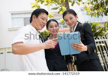 Close-up of a couple and a realtor using a tablet outside - stock photo