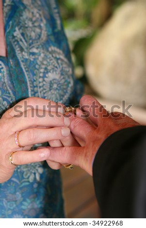 Close-up of a couple exchanging wedding rings during a ceremony.