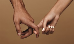 Close up of a couple linking index fingers. Man and woman in love linking index fingers against brown background