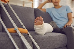 Close up of a crutches and a broken leg in a plaster cast of a woman sitting on a sofa and resting. Concept of rehabilitation after injury. Selective focus.