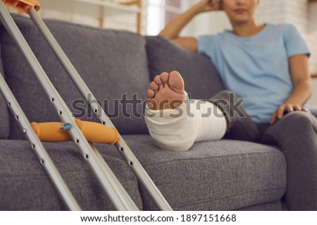 Close up of a crutches and a broken leg in a plaster cast of a woman sitting on a sofa and resting. Concept of rehabilitation after injury. Selective focus. Stock photo ©