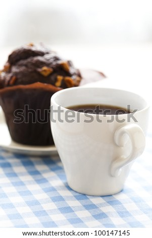Close-up of a cup of black coffee and a chocolate muffin.