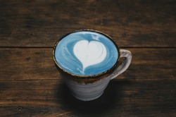 Close-up of a cup of Blue latte on wooden table. The vibrant blue colour of the drink is natural, Made from micro-milled Butterfly Pea Flower, which originated in Thailand.