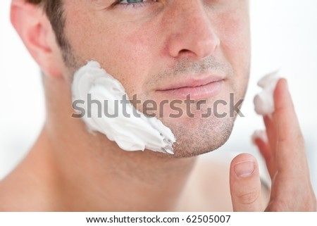 Close-up of a cute man preparing to shave in the bathroom at home