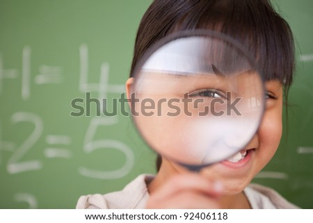 Close up of a cute schoolgirl looking through a magnifying glass in a classroom