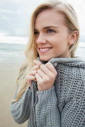 Close up of a cute smiling young woman in gray knitted jacket on the beach