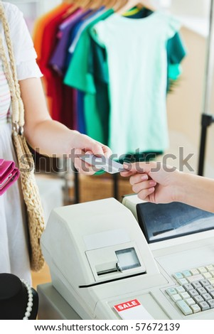 Close-up of a cute woman paying with her credit card in a shop