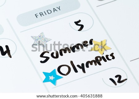 close up of a daily planner or calendar with a hand written message for a celebration or holiday like the beginning of the summer Olympics