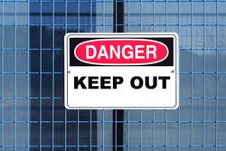 Close up of a danger keep out sign hanging on mash metal fence outside of construction site.