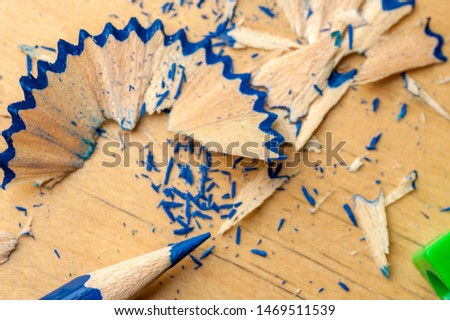 Close-up of a dark blue pencil just been sharpened with a sharpener lying next to wooden shavings on a table. The concept of creativity of children and artists