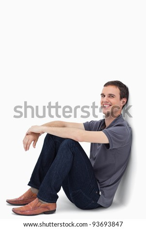 Close-up of a dark brown hair man smiling while sitting against a wall with white background