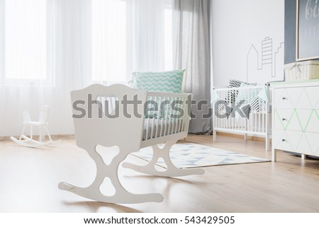 Close-up of a decorative white cradle in a very bright baby room #543429505