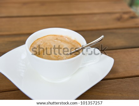 close up of  a delicious cup of coffee on wooden table.