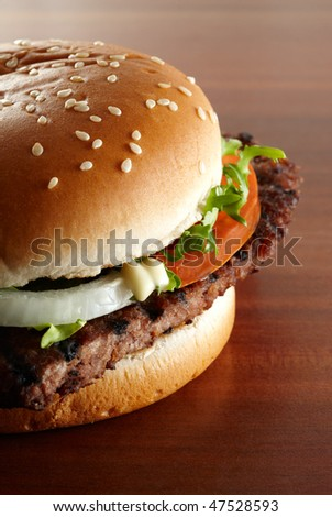 close-up of a delicious hamburger with salad and tomato on wood grain