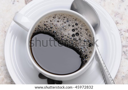 Close up of a delicious hot cup of coffee with spoon horizontal format overhead view
