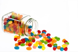 Close up of a delicious Jelly Beans candy spilled from a glass jar isolated on a white background