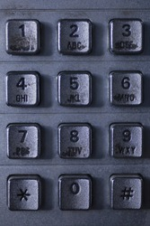 Close up of a dirty public telephone metal keypad. Macro view of the buttons and digits of a public phone keypad.
