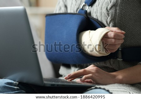 Close up of a disabled woman hands using laptop with a broken arm in a sling on a couch at home Photo stock ©