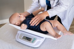 Close up of a doctor checking weight of cute little baby boy. Lovely pediatrician weighing adorable baby in her office. Cute little toddler lying on scales for medical checkup.