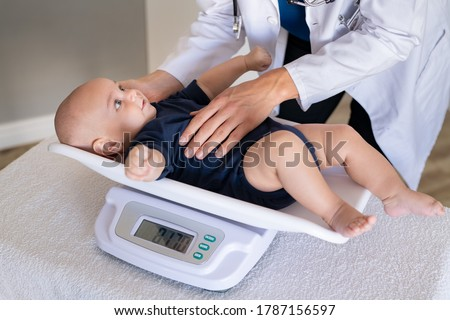 Close up of a doctor checking weight of cute little baby boy. Lovely pediatrician weighing adorable baby in her office. Cute little toddler lying on scales for medical checkup. Foto d'archivio ©
