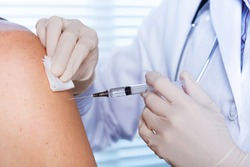 Close up of a Doctor making a vaccination in the shoulder of patient