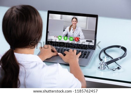 Close-up Of A Doctor Video Conferencing With Female Colleague On Laptop In Clinic