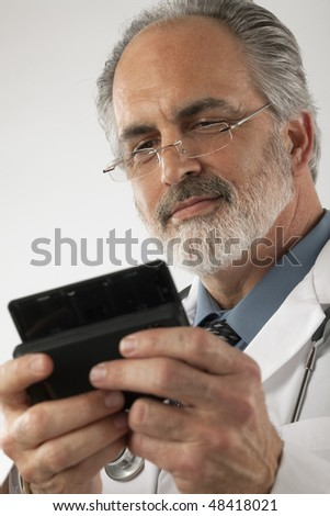 Close-up of a doctor wearing glasses and a lab coat and texting on a cell phone. Vertical shot.