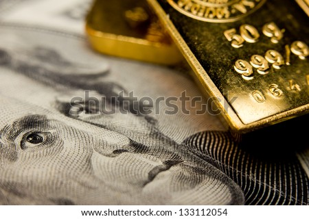 Close-up of a 20-dollar banknote and gold bullions - stock photo