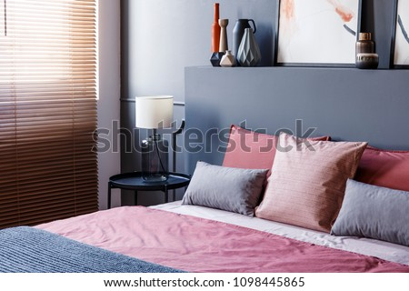 Close-up of a double bed decorated with pillows in a hotel room interior with grey wall, lamp, vases and window blinds #1098445865