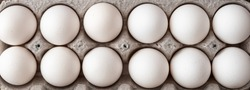 Close up of a dozen eggs in cardboard egg carton, food background
