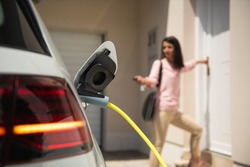Close up of a electric car charger with female silhouette in the background, entering the home door and locking car