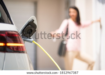 Close up of a electric car charger with female silhouette in the background, entering the home door and locking car Stockfoto ©