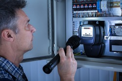 Close-up Of A Electrician Examining A Fusebox With A Torch
