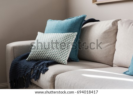 Close up of a fabric sofa with styled cushions and throw #694018417