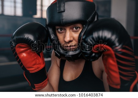 Stock Photo Close up of a female boxer in her boxing gear. Woman boxer at a boxing studio wearing head guard and boxing gloves.