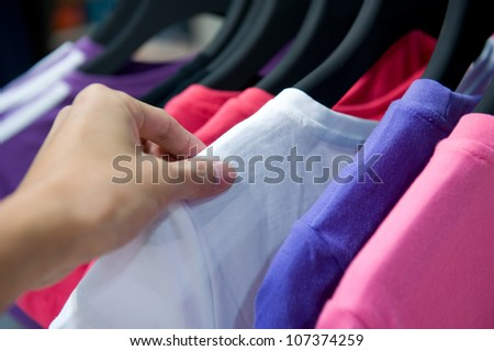 Close-up of a female customer looking for T-shirts in a fashion store