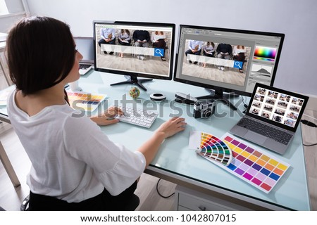 Close-up Of A Female Designer Working On Multiple Computer At Workplace
