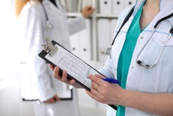 Close-up of a female doctor while filling up medical application form