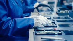 Close Up of a Female Electronics Factory Worker in Blue Work Coat and Protective Glasses Assembling Smartphones with Screwdriver. High Tech Factory Facility with more Employees in the Background.