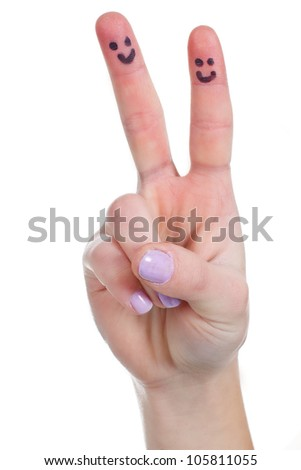 Close-up of a female hand showing sign of victory with funny faces drawn on the fingers - isolated on white