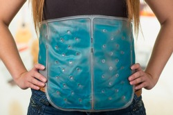 Close up of a female holding ice gel pack on her belly, medical concept, in office background