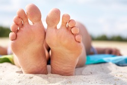 Close-up of a female lying on beach barefoot