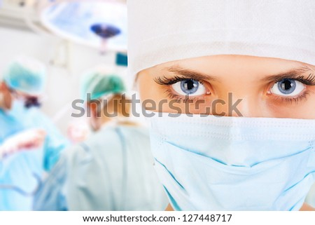Close-up of a female surgeon with his team in operation room