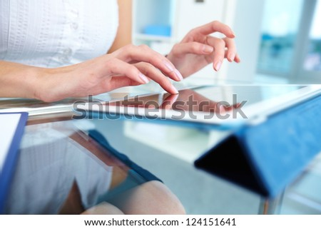 Close-up of a female touching the screen of a tablet computer