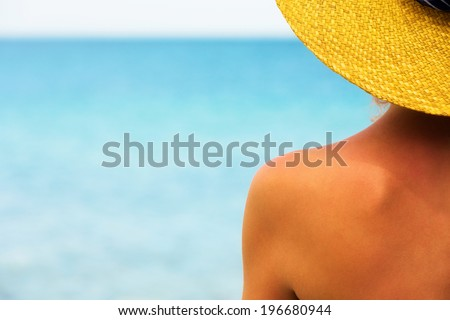 Close up of a female wearing a hat at the beach . #196680944